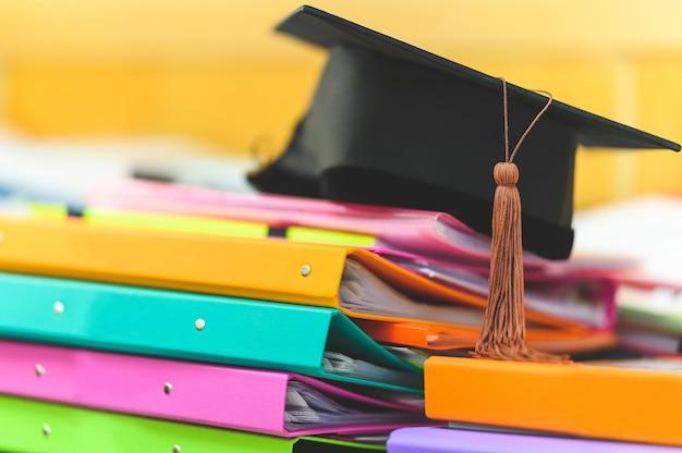 Black graduation cap placed on a file folder on a desk