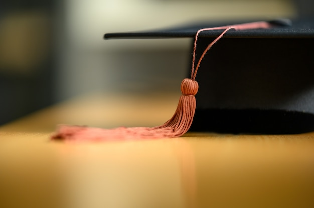 Black graduation cap placed on a wooden table