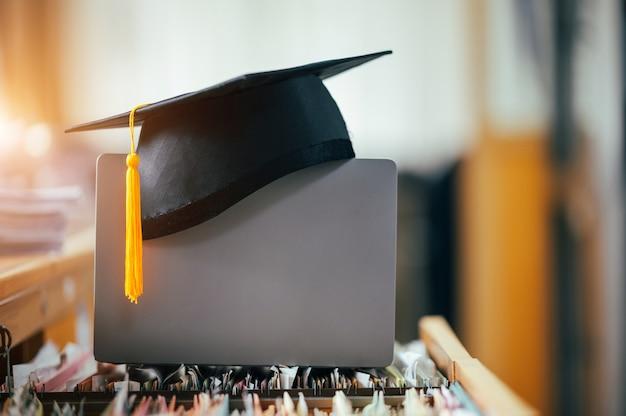 ノートパソコンに黄色のタッセルが付いた黒い卒業帽