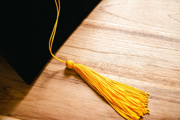 Black graduation cap and yellow tassel place on wooden table