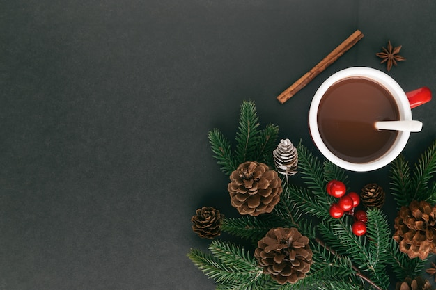 Black granite table decorate pine leaf and pine cones, holly balls and cup of hot chocolate or cacao in christmas drink concept