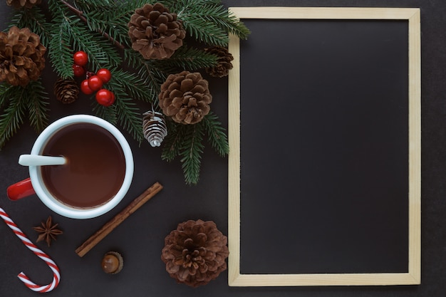 Black granite table decorate with blackboard or chalkboard, pine leaf and cones and cup of chocolate in christmas concept