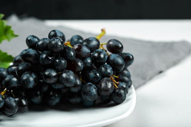 Черный виноград с листьями на белой тарелке с серой скатертью. фото высокого качества