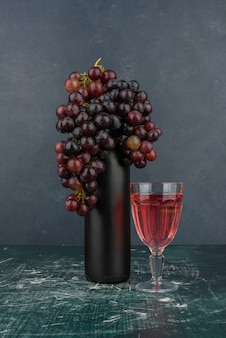 Black grapes around a bottle and glass of wine on marble table.