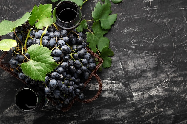 Black grapes basket and glass of red wine on dark rustic concrete background. flat lay wine composition red wine glass or grape juice on black stone table with copy space.