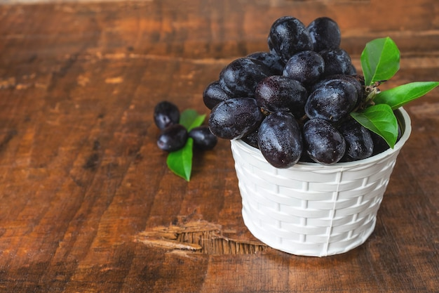 Black grapes in a basket on a wooden table