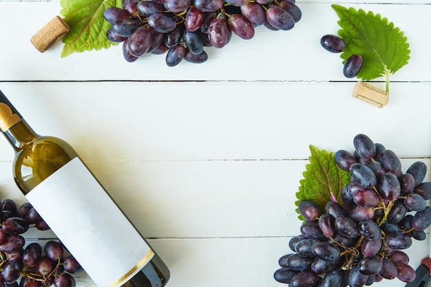 Black grapes and a bottle of wine on a light table