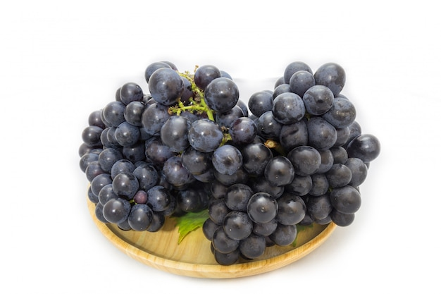 Black grapes bunch isolated on wooden plate and white background with green leaf package