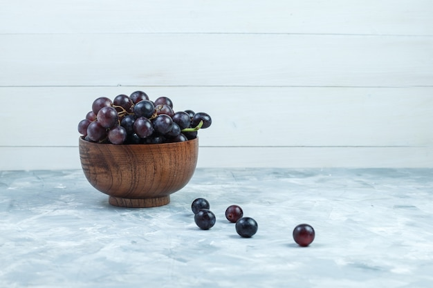 Black grapes in a clay bowl on grungy grey and wooden background. side view.