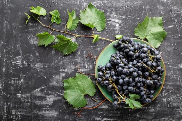 暗いテーブルトップビューにつる植物とプレートの黒ブドウ。黒いコンクリートの背景に甘いジューシーなブドウの食べ物は、コピースペースで平らに横たわっていました。