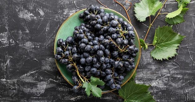 Black grapes in plate with vine plant on dark table top view. sweet juicy grapes food on black concrete background flat lay. long web banner.