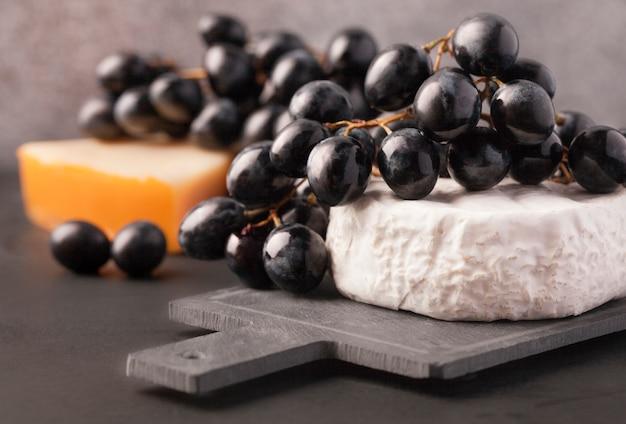 Черный виноград с мягким французским сыром на доске в качестве закуски для вина
