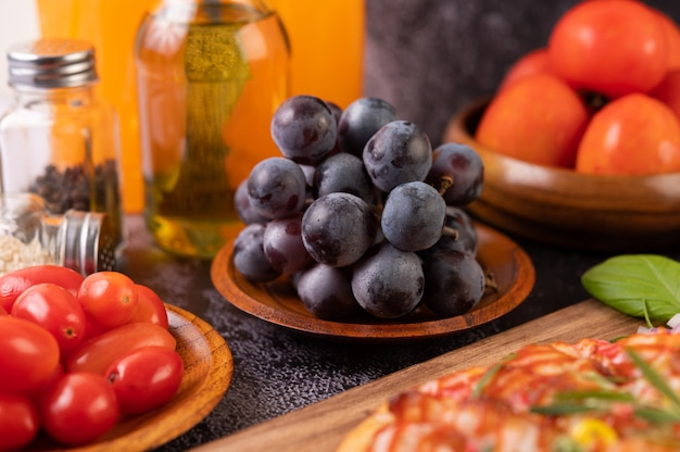Black grapes on a wooden plate with tomatoes orange juice and pizza.