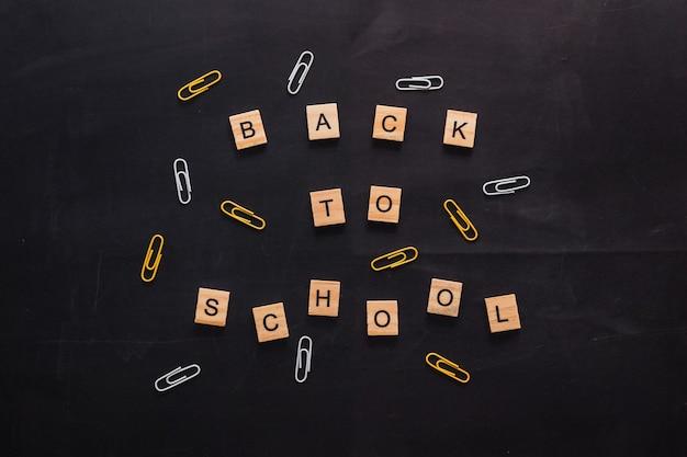 Черная графитовая доска с надписью деревянными буквами обратно в школу возле канцелярского цвета ...