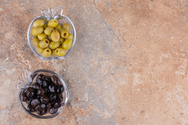 Black and green marinated olives in glass cups