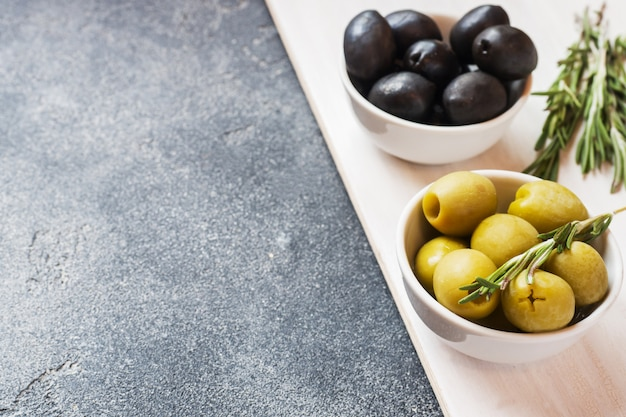 Black and green olives in bowls on dark table