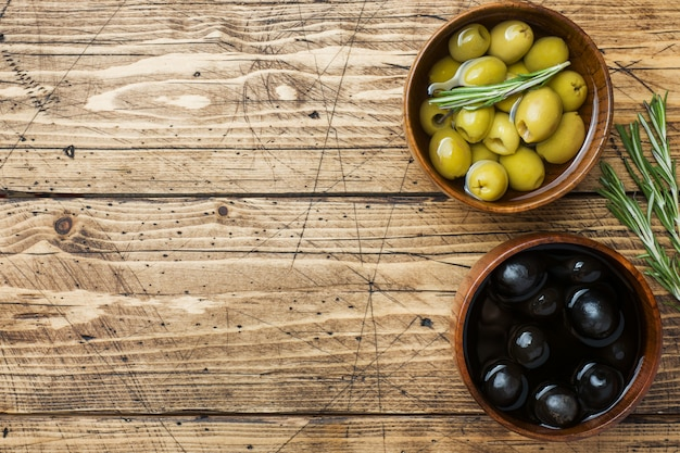 Black and green olives in wooden bowls on wooden table
