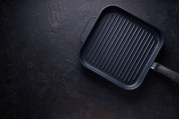 Black grill pan on dark stone background top view