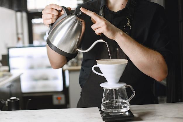 黒挽いたコーヒー。バリスタは飲み物を醸造します。ガラスの水差しのコーヒー。