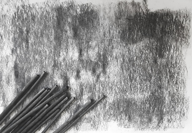 Black grunge coal ink sheet of paper background and crayons