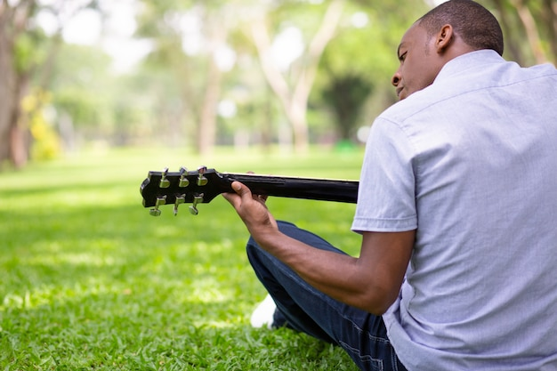 Black guitarist sitting on grass and playing guitar in park