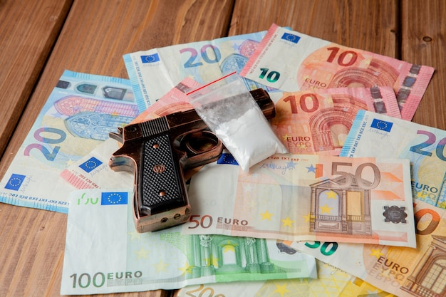 Черный пистолет и пакеты с наркотиками на фоне евро на деревянном столе