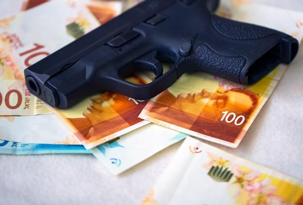 스택 돈에 검은 총 권총 테이블에 이스라엘 새 셰켈 지폐입니다. new israel shekel 100, 200 nis 지폐가 있는 반자동 권총 총기. 통화, 범죄 돈 개념입니다. 불법 판매.