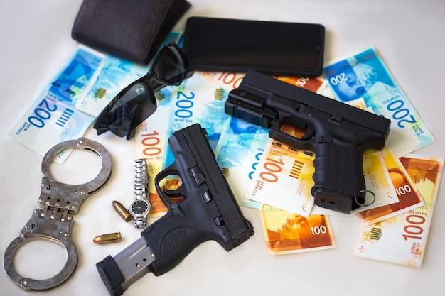 弾薬、手錠、サングラス、腕時計、携帯電話を備えた黒い銃のピストルが、テーブルにイスラエルの新シェケル紙幣を置いています。新シェケル紙幣を備えた半自動拳銃銃器