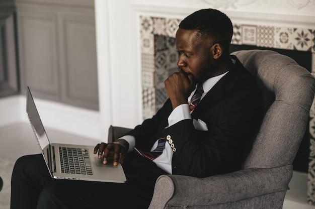 Черный парень в черном костюме пристально смотрит на ноутбук. фото высокого качества
