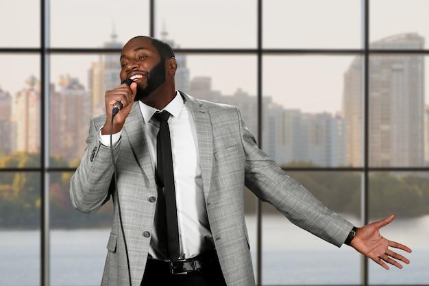 Черный парень поет в микрофон.
