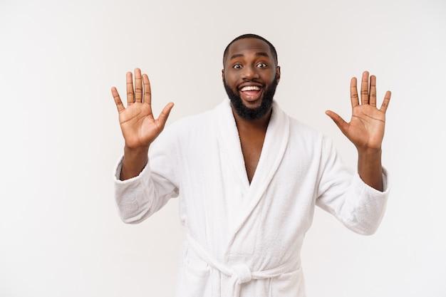 驚きと幸せな感情でバスローブ人差し指を身に着けている黒人の男。