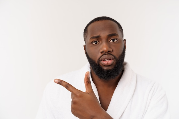 Black guy wearing a bathrobe pointing finger with surprise and happy emotion.