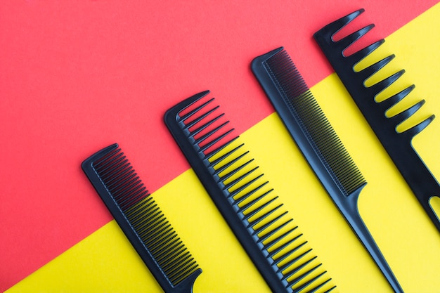 Black hair combs on the bicolor background. top view. copy space.