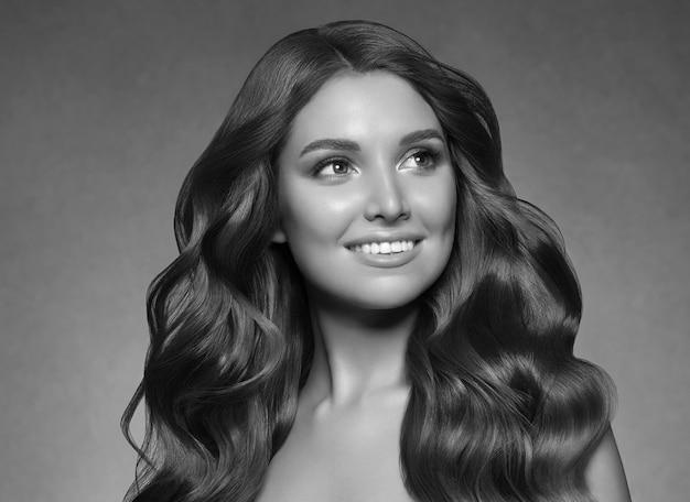 黒髪の女性の長い巻き毛の美しさの化粧品の概念を黒の背景に。スタジオショット。グレー。黒と白。モノクロ。