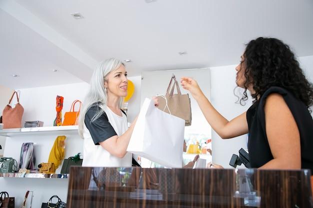 黒髪の洋服店のレジ係がレジ付きの机の上で顧客に紙袋を渡します。側面図。ショッピングや消費主義の概念