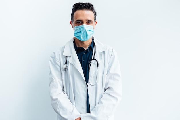 Черноволосый доктор в хирургической маске, с белым халатом и стетоскопом, глядя на камеру, на белом фоне.