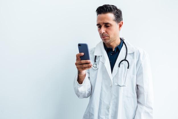 Черноволосый доктор в белом халате и стетоскоп, глядя на его мобильный телефон, на белом фоне.