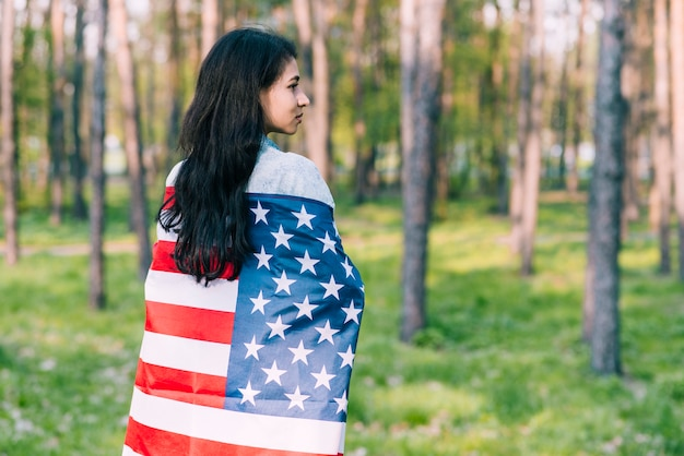 Black-haired female wrapped in flag of usa