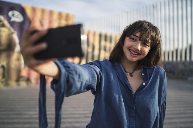 Черноволосая девушка фотографирует себя за зданием