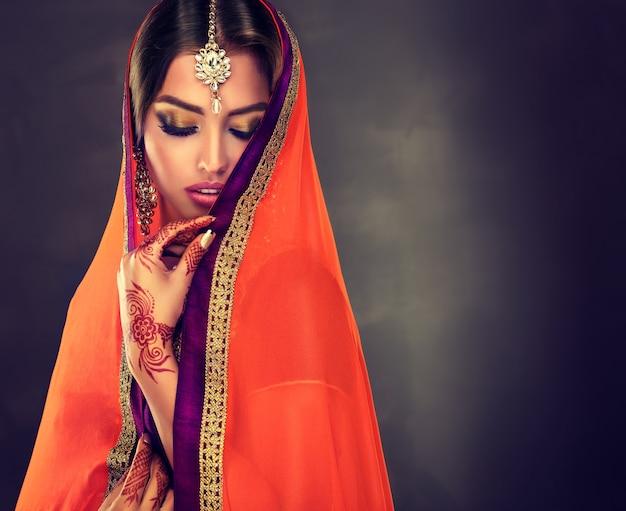 伝統的なファッショナブルな衣装に身を包んだ黒髪のインドの若い女性サリー金色のまぶた、手にヘナの入れ墨、地元のインド風ジュエリーオリエンタルビューティーを備えた素晴らしいメイク