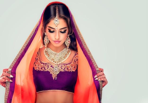 전통적인 유행 의상을 입고 검은 머리 인도 젊은 여자