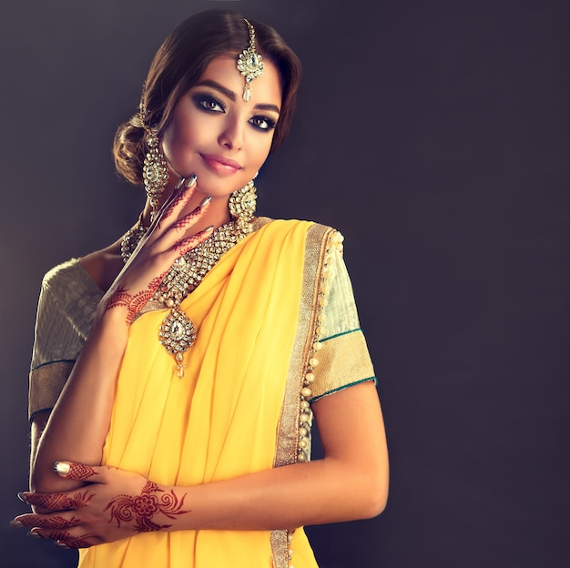 Black haired indian young woman dressed in a posh yellow sari model dressed in a traditional national suit mehndi henna tattoo is painted on her hands and traditional kundan style jewelry set