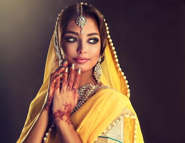 豪華な衣装を着た黒髪のインドの若い女性lehengacholiベールに包まれた頭の素晴らしいメイクと豪華なインドのジュエリーセットインドの美しさ