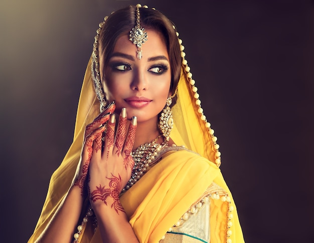 Black haired indian young woman put on in a posh outfit lehenga choli veiled head splendid makeup and posh indian jewellery set indian beauty