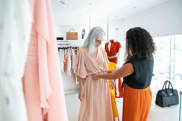 Assistente di negozio dai capelli neri che aiuta la donna a provare il nuovo vestito e la regolazione della cintura. cliente che sceglie i vestiti nel negozio di moda. acquisto di vestiti nel concetto di boutique