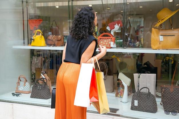 검은 머리 여자 구매 가방을 들고, 상점 창에서 쳐다보고, 외부 상점에 서. 다시보기. 윈도우 쇼핑 개념