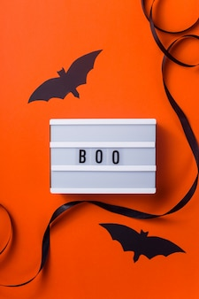 Black halloween characters and accessories on a bright orange surface