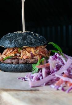 牛カツ、ベーコン、トマト、きゅうり、赤玉ねぎのブラックハンバーガー。前景のサラダコールスロー。閉じる。暗い背景。
