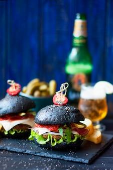 쇠고기, 샐러드, 감자 튀김과 검은 햄버거. 유리에 신선한 맥주입니다. 길거리 음식의 동향. 칼로리 저녁. 공간 복사