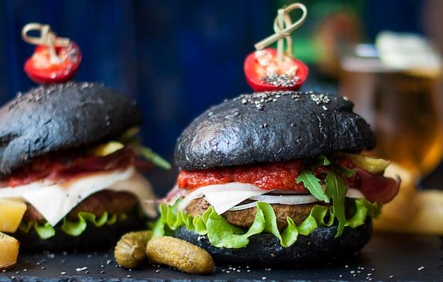 쇠고기, 샐러드, 감자 튀김과 검은 햄버거. 길거리 음식의 동향. 칼로리 저녁. 패스트 푸드. 공간 복사